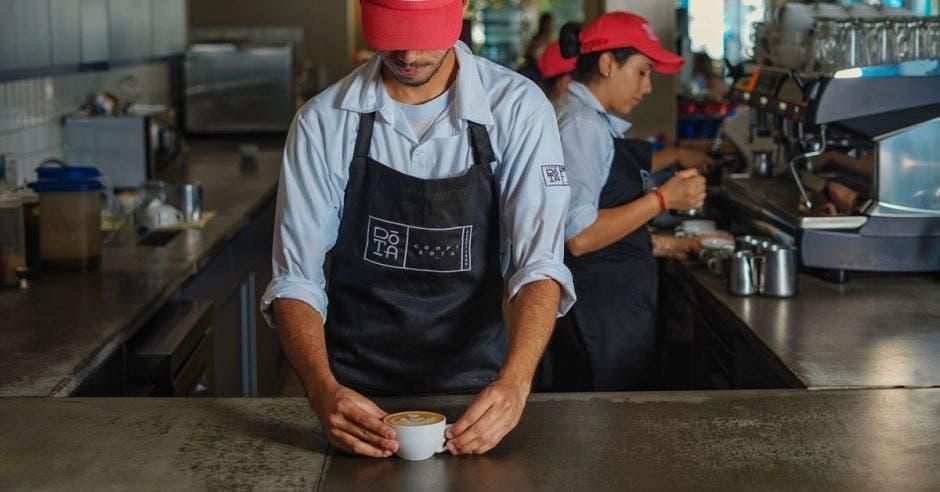 un hombre sirve café en una taza