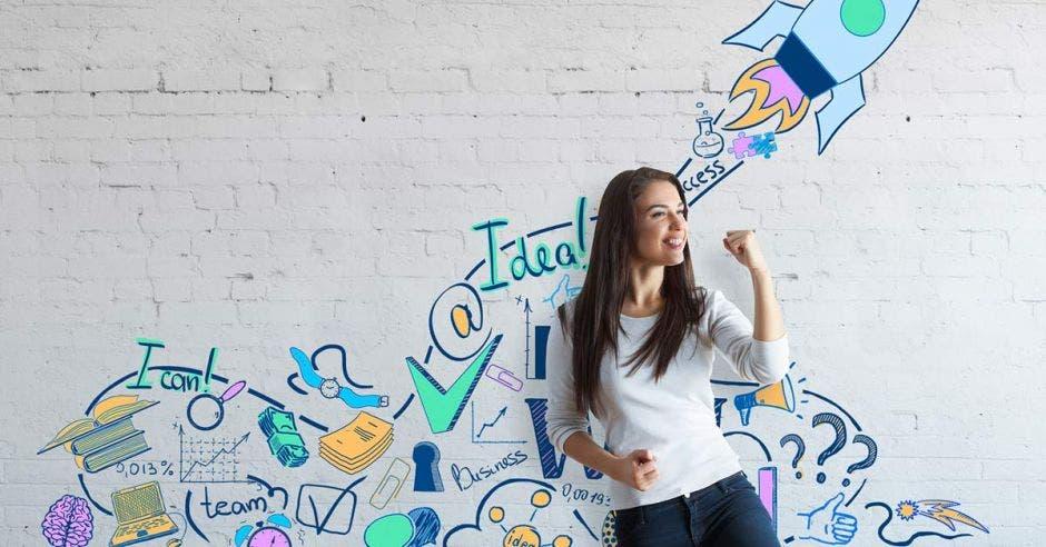 mujer joven con puño cerrado y brazo encogido, detrás de ella pared con dibujos referentes a ideas de negocio