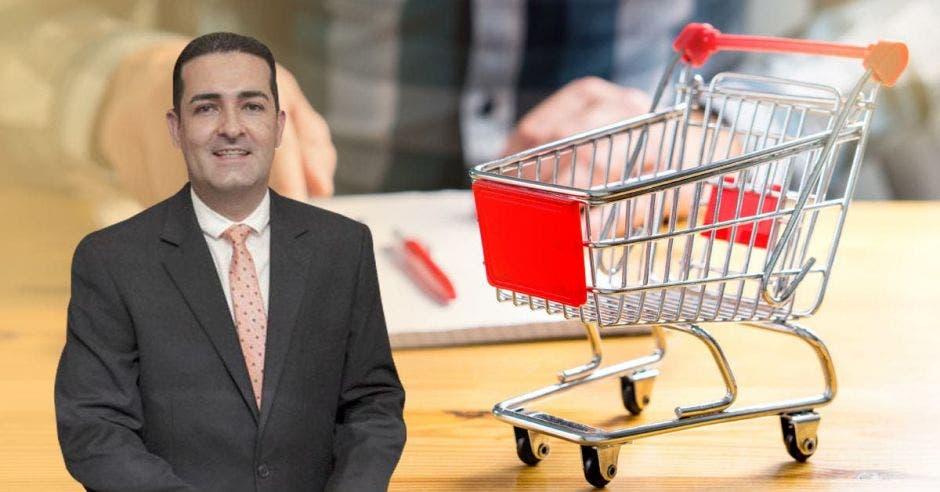 Hombre de traje y corbata frente a carrito de supermercado pequeño
