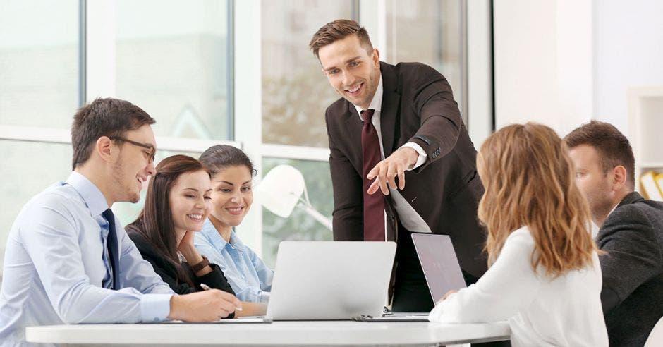 hombres y mujeres jóvenes en una reunión de trabajo viendo laptop