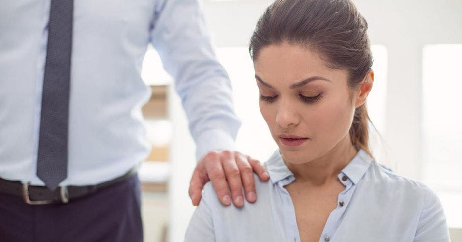 mujer incómoda al tener la mano de compañero sobre su hombro