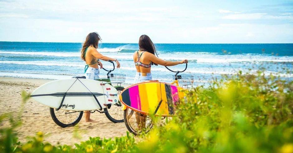 dos mujeres en bicicleta llevan consigo una tabla de surf