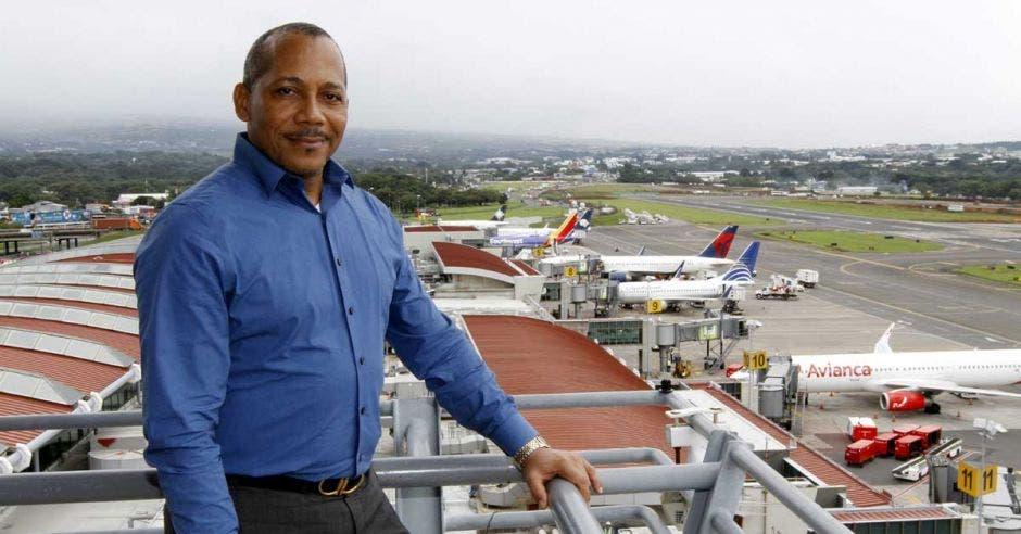 un hombre de camisa azul y pantalón gris posa sobre el fondo de un aeropuerto en operaciones