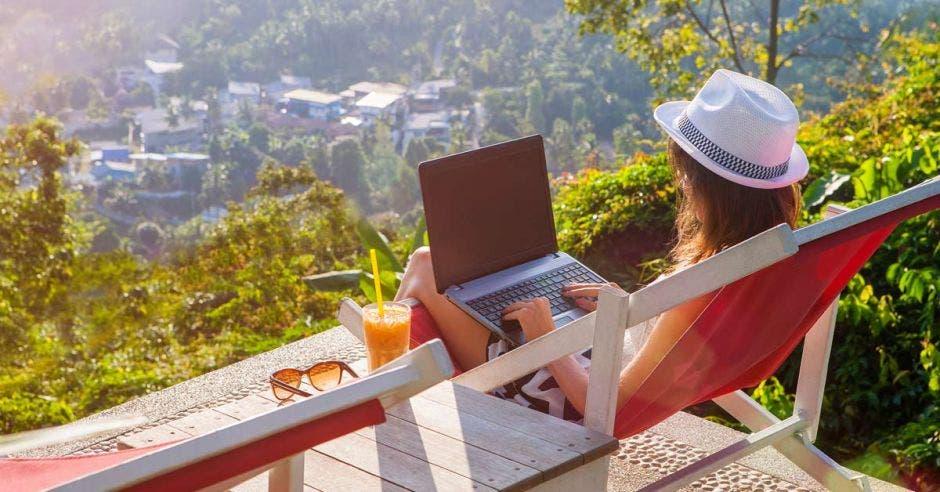 una mujer usa una computadora en un balcón