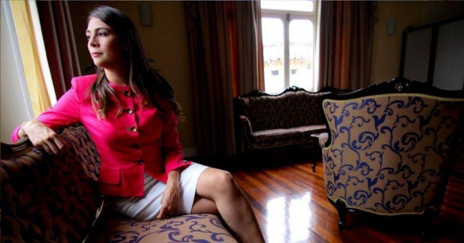 Mujer de rosado sentada en sillón
