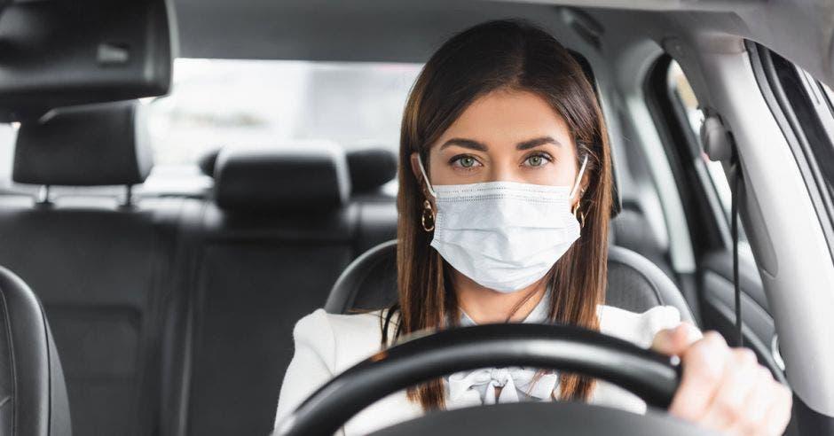 mujer joven usando mascarilla, manejando automóvil