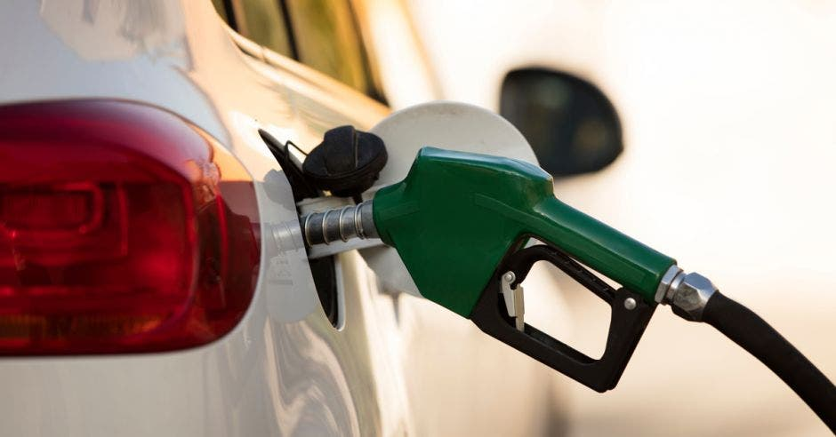 una pistola de gasolina color verde alimentando un carro color blanco