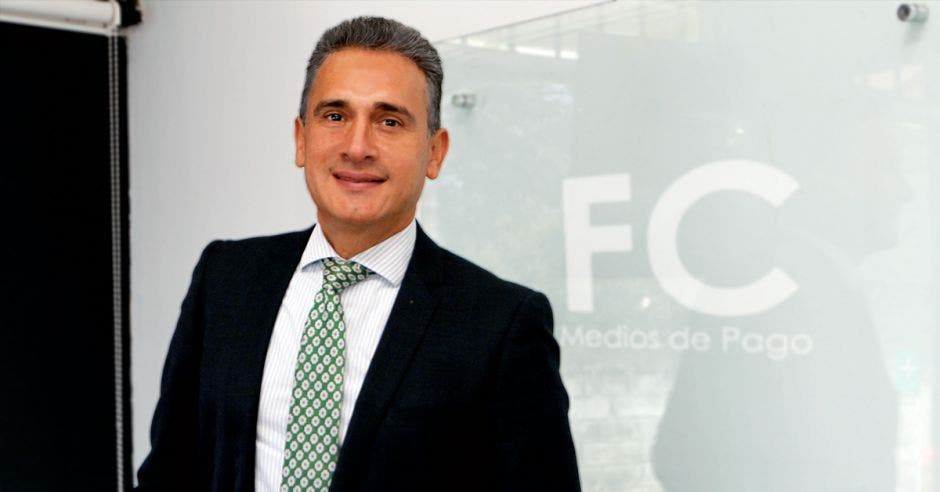 hombre canoso con saco negro, camisa blanca y corbata verde
