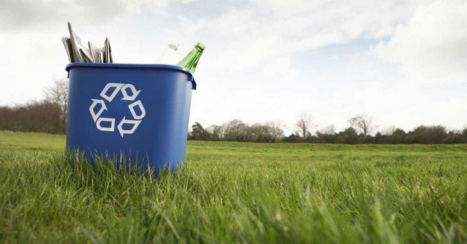 un bote de basura azul con material de reciclaje adentro, como botellas de vidrio, periódico y cartón
