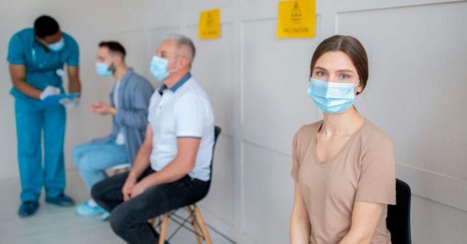 personas en fila esperando a ser vacunadas