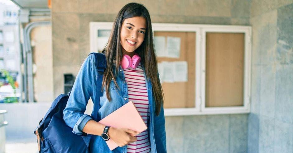 mujer joven estudiante con audífonos y libreta rosa en mano