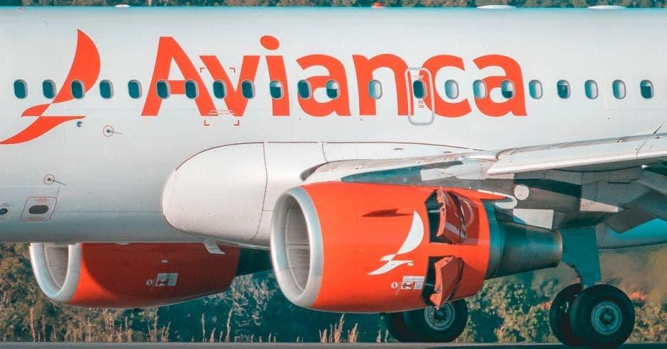 un avión blanco con ribetes rojos que dice avianca