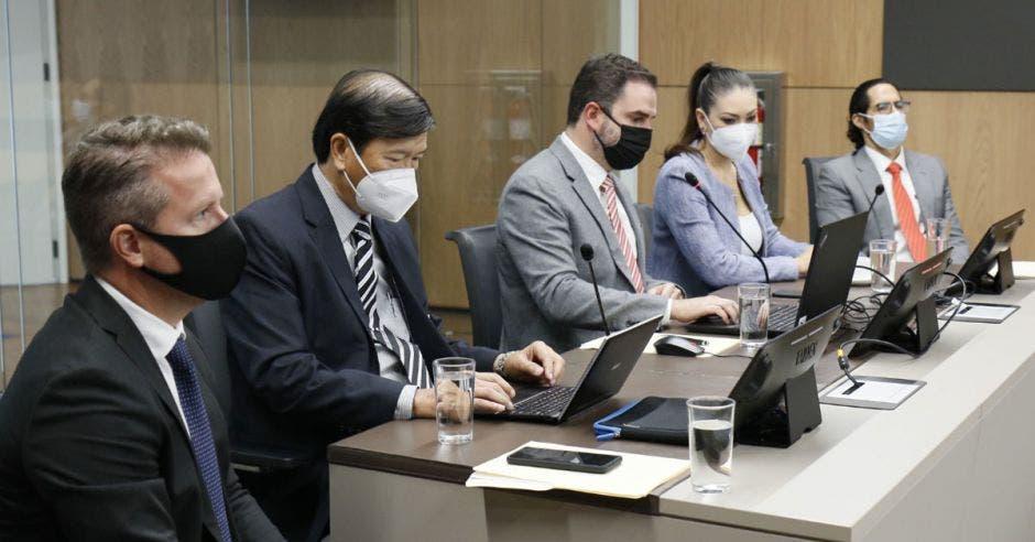 un grupo de hombres con saco y corbata discutiendo en un edificio