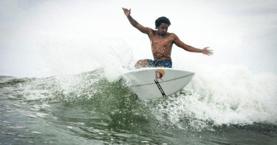 un hombre moreno surfeando con una tabla color blanco