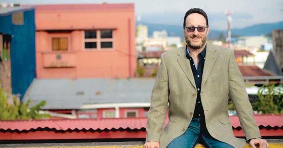 un hombre de saco beige y camisa negra sentado en el tejado de un edificio