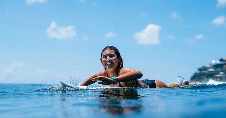 una mujer en vestido de baño sobre una tabla de surf color blanco