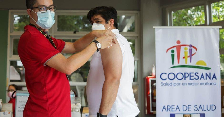 un hombre de mediana edad está siendo vacunado por hombre joven de camisa roja