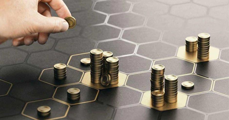 Mano de persona poniendo monedas en distintos lugares