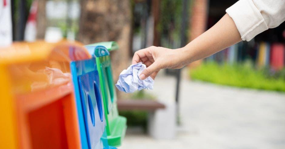 Una mujer deposita basura en contenedores de reciclaje multicolor
