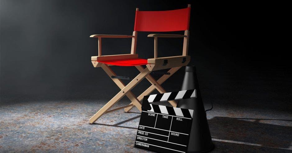 una silla de director de cine color rojo junto a una claqueta