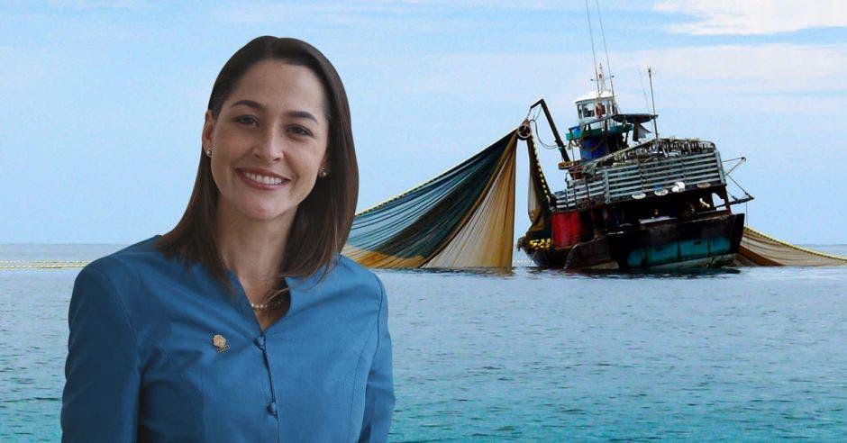 una mujer de traje azul sobre un fondo que contiene el mar y un barco atunero