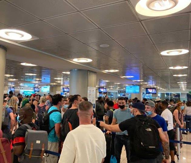 un grupo de personas conglomeradas en un salón de espera de un aeropuerto