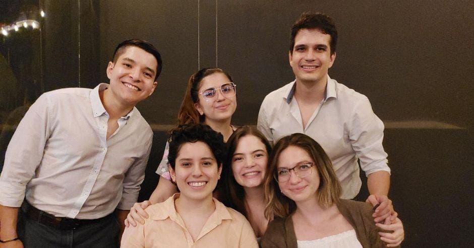 un grupo de seis personas de camisas blancas y beige. Dos hombres y tres mujeres.