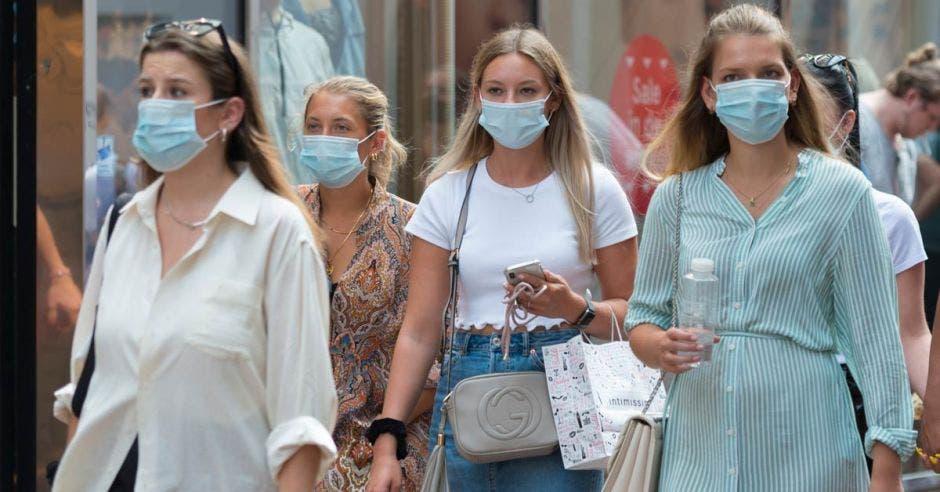 chicas de compras en la calle Kalverstraat, centro de la ciudad de Ámsterdam, con una mascarilla relacionada con el brote de Covid 19 / coronavirus