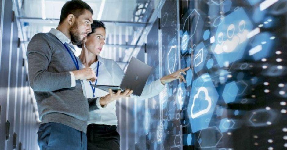 Mujer y hombre viendo datos tecnológicos en la nube