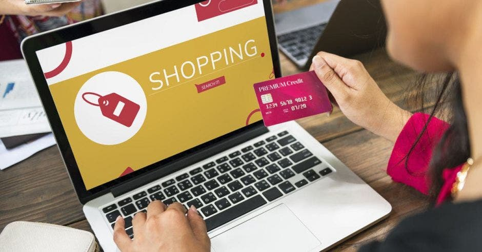 Mujer con tarjeta compra a través de su laptop