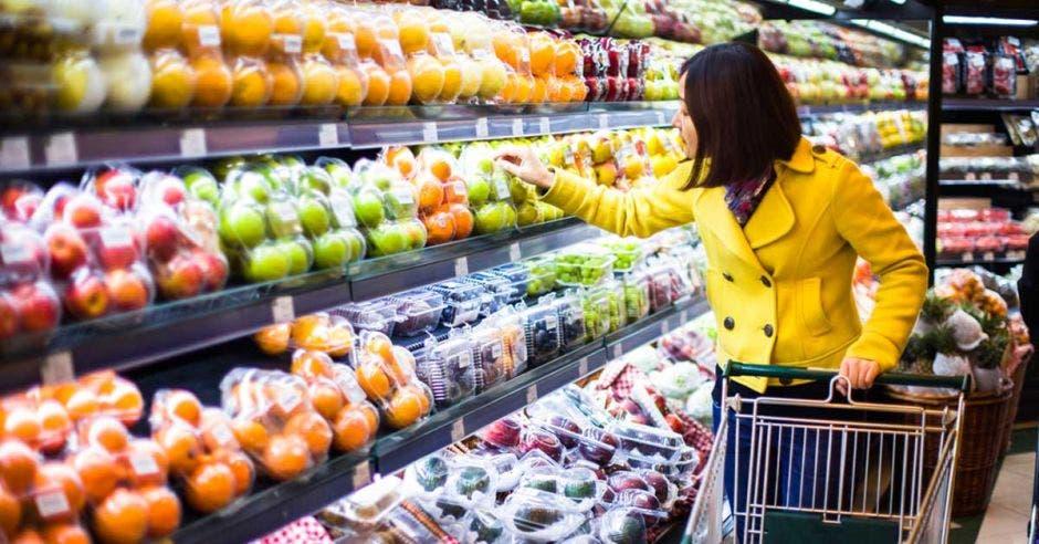 Mujer de amarillo con canasta en supermercado viendo frutas