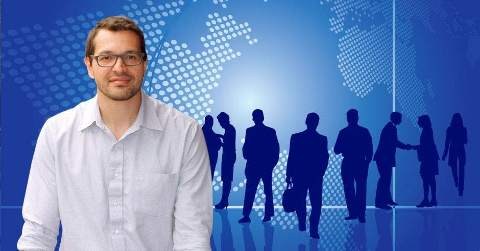 Hombre de blanco con lentes ante dibujo de siluetas de personas en planeta