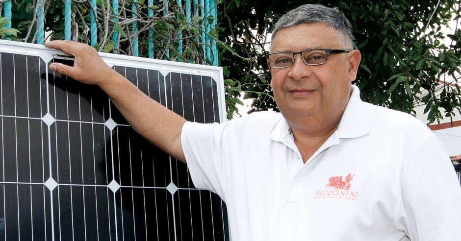 Hombre canoso de lentes con camisa blanca, junto a panel solar