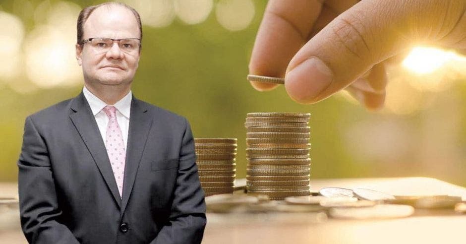 Hombre de traje frente a monedas apiladas por mano