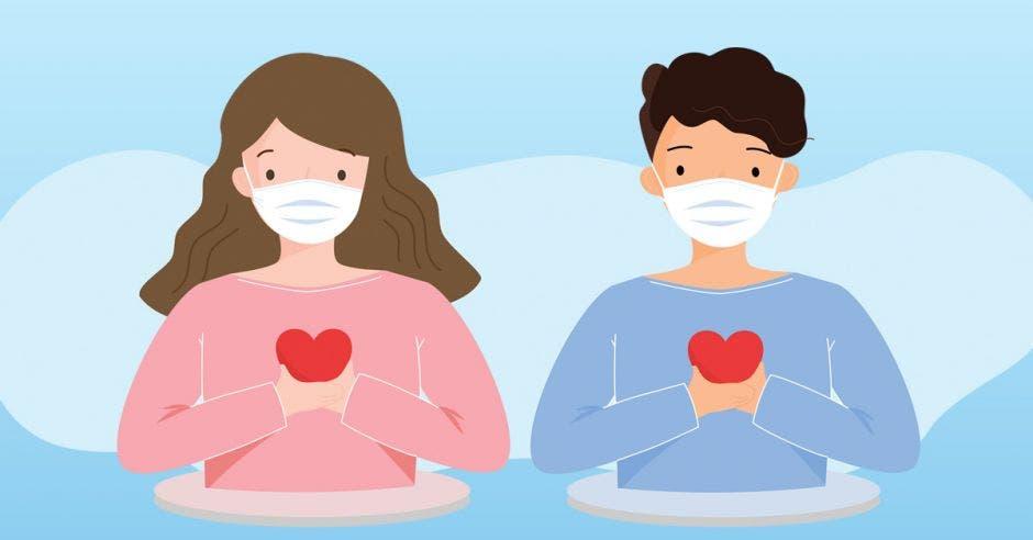 hombre y mujer con mascarilla y un corazón entre las manos