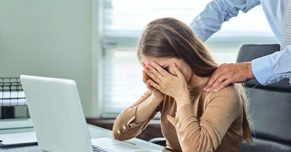 Un hombre toca la espalda de una mujer, mientras ella se lamenta