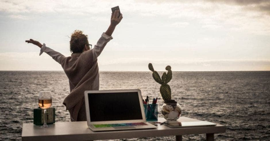 nómada digital trabajando en la playa con brazos extendidos