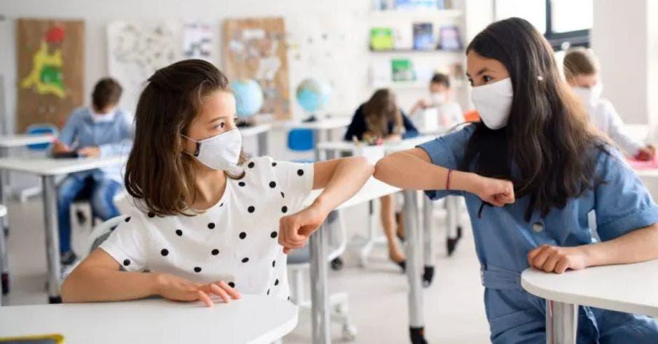dos estudiantes en el aula pegando codo con codo, y ambas con mascarilla