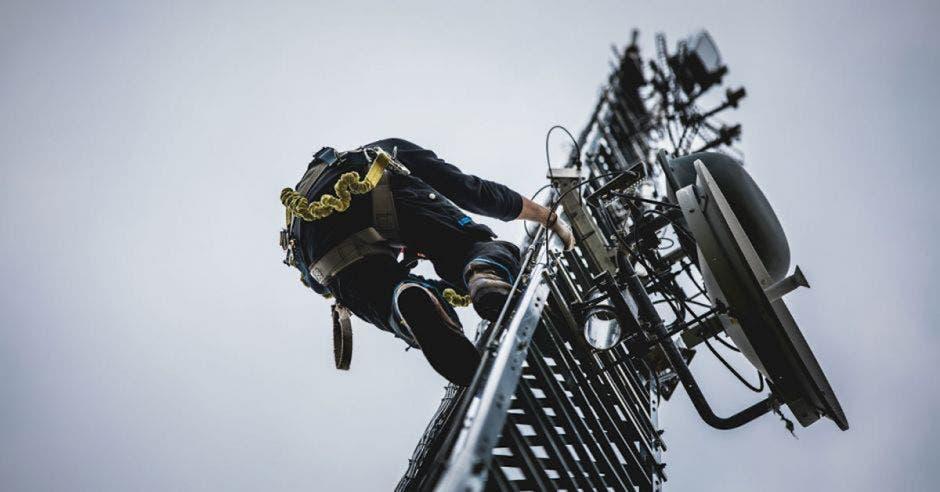 Técnico escalando torre celular