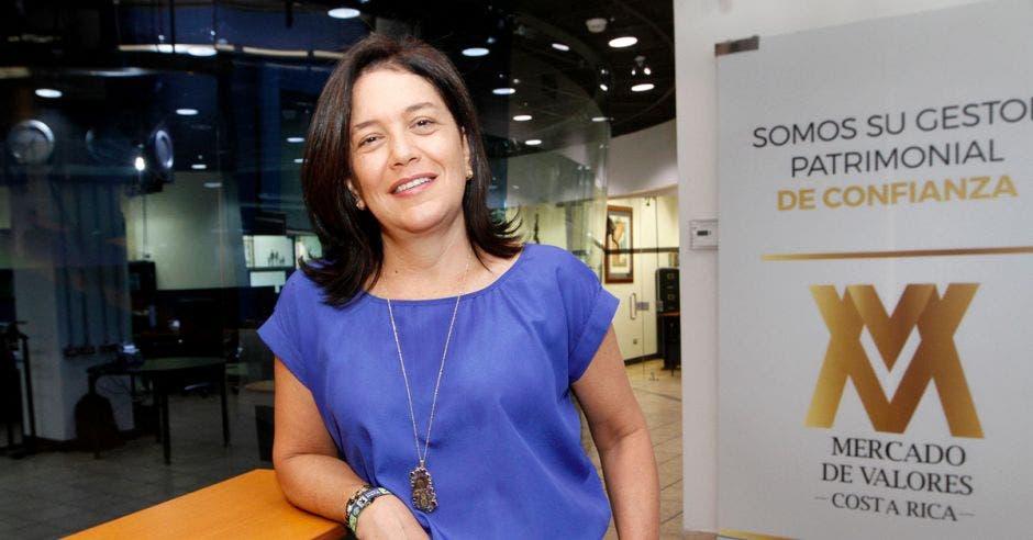 Mujer de azul frente a logo de Mercado de Valores