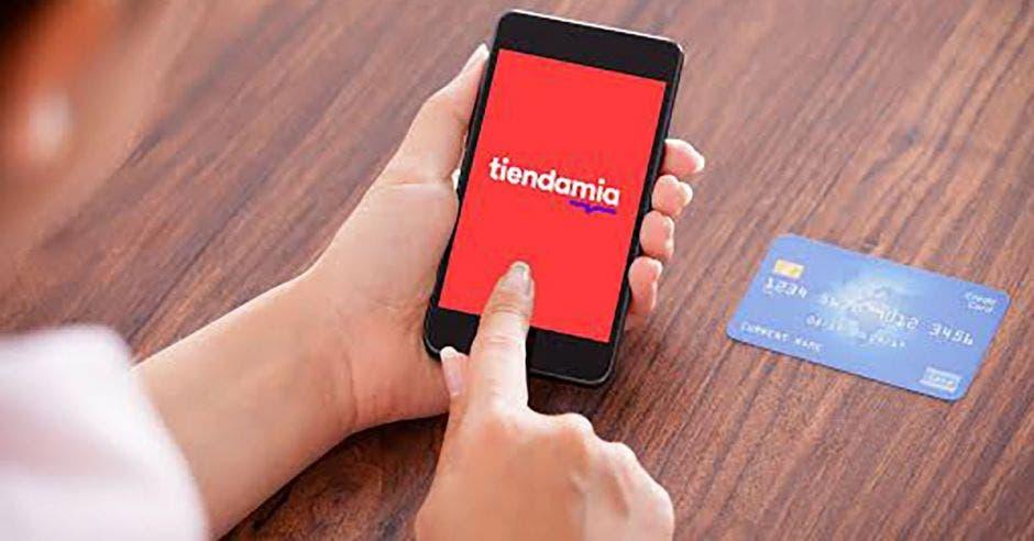 Una persona manipulando la aplicación con una tarjeta de crédito al lado.