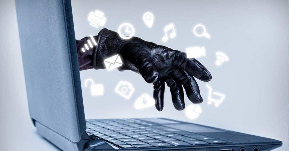 Mano con guante saliendo de pantalla de laptop
