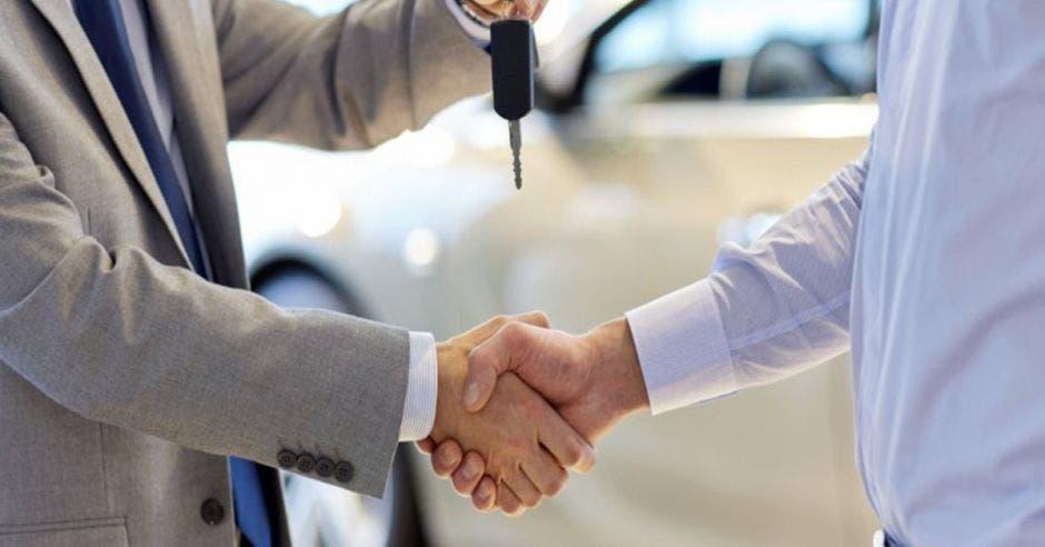Personas con apretón de manos y una da llaves de un carro a la otra