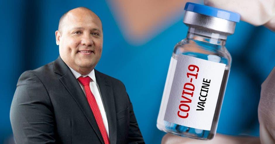 Mario Ruiz, gerente médico de la Caja, con un frasco de vacuna de fondo.