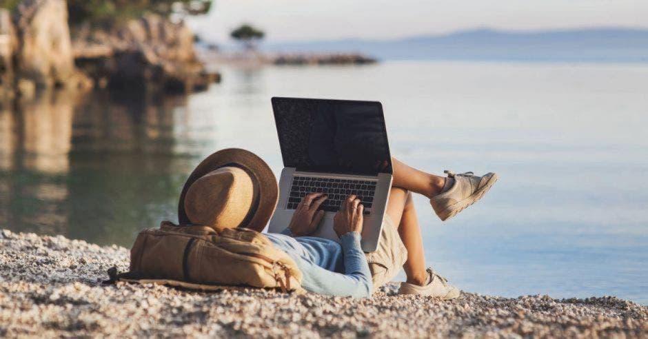 hombre sosteniendo computadora en la playa.