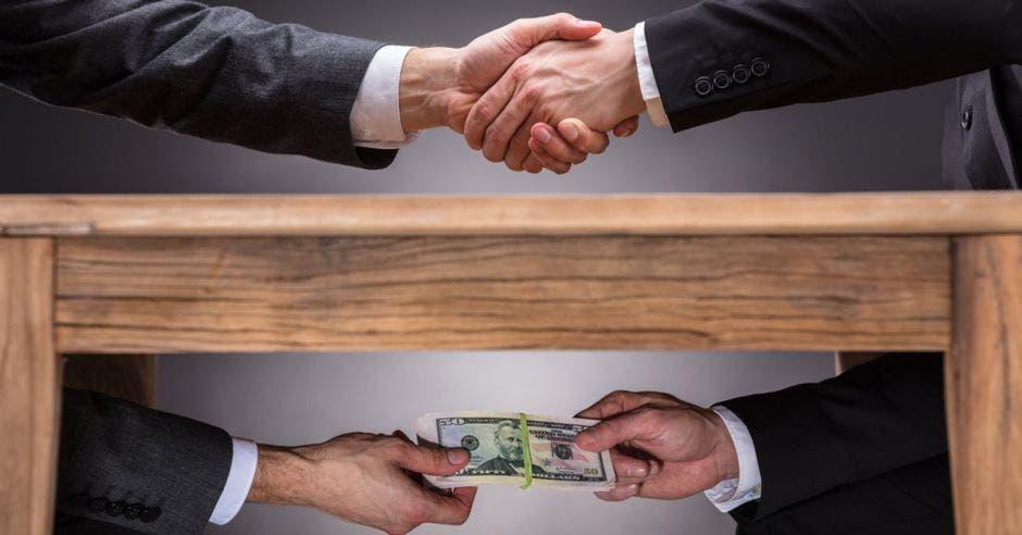 Foto ilustrativa que muestra a dos personas dándose la mano sobre la mesa y pagando una mordida debajo de la mesa