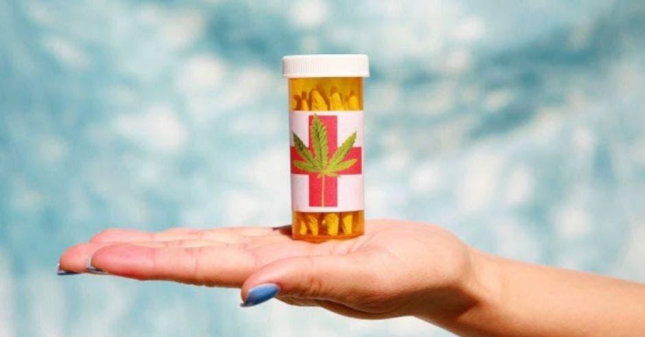 mano extendida encima bote con porros de marihuana para uso medicinal