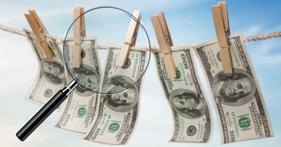 Dólares en ganchos y lupa