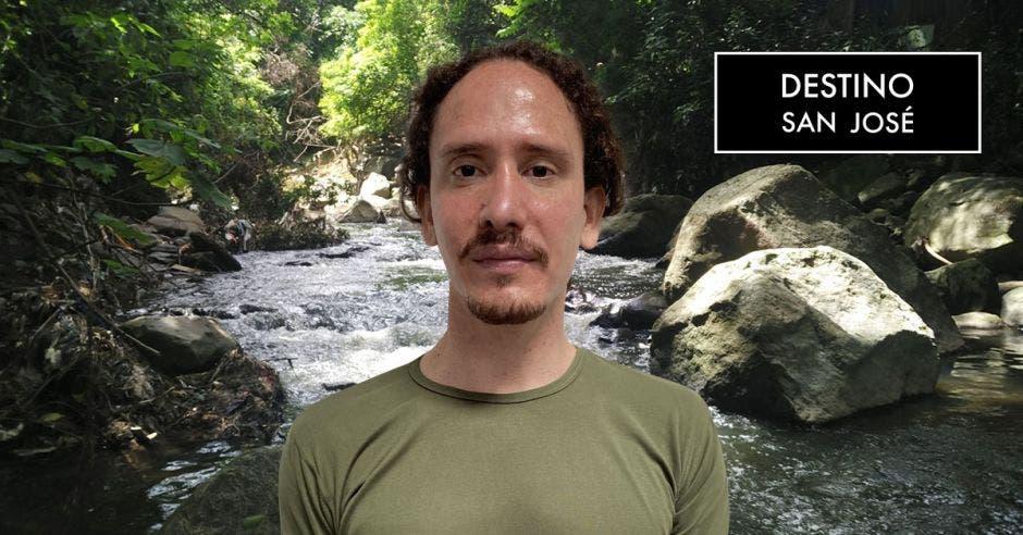 hombre de cabello castaño, barba y bigote con playera verde olivo de fondo imagen de río