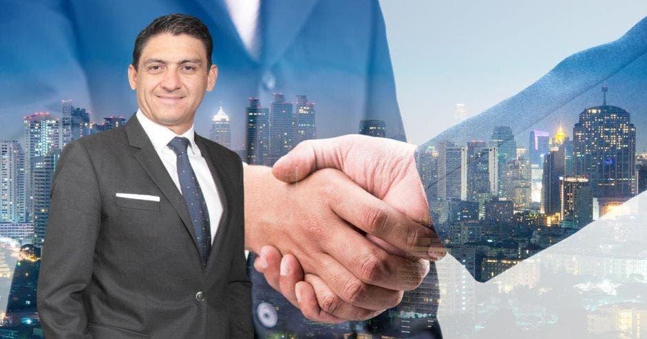 Hombre de traje frente a personas dándose apretón de manos